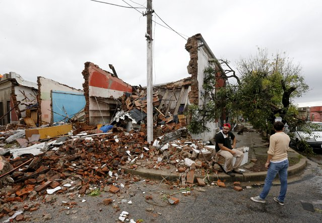 People look on next to debris at a street in Dolores, the day after the city was hit by a tornado, April 16, 2016. (Photo by Andres Stapff/Reuters)
