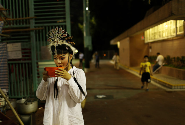 """A Chinese opera actress drinks a bowl of soup before her performance at a makeshift theater during the """"Hungry Ghost Festival"""" in Hong Kong, Tuesday August 20, 2013. The Hungry Ghost Festival is celebrated during the seventh month in the Chinese lunar calendar.  (Photo by Vincent Yu/AP Photo)"""
