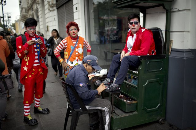 A clown has his shoes shined during a march commemorating the Peruvian clown day in Lima Peru, Monday, May 25, 2015. Hundreds of professional clowns dressed in colorful costumes, wigs and face paint marched through the streets of Lima to celebrate Peruvian Clown Day. (Photo by Rodrigo Abd/AP Photo)