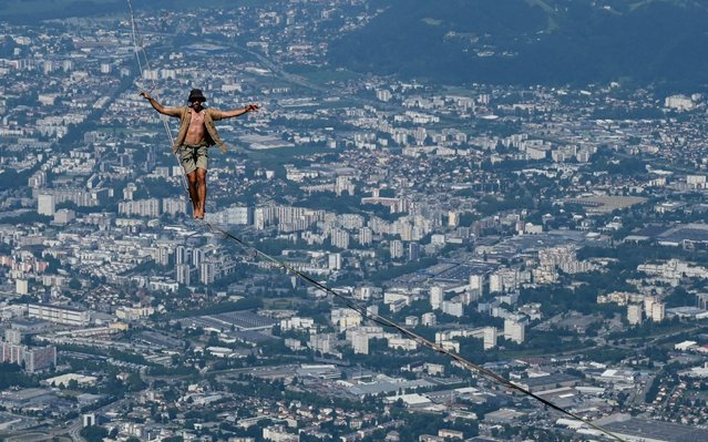 "A man walks on a slackline during the 7th edition of the European ""Marmotte Highline Project"" (MHP) festival in Lans-en-Vercors, near Grenoble, eastern France, on July 4, 2019. The event, during which the participants will be able to evolve on the various highlines located in the Regional Natural Park of Vercors, takes place until July 7, 2019. (Photo by Philippe Desmazes/AFP Photo)"