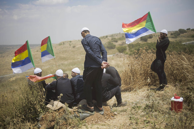 Members of Israel's Druze minority look at the fighting between forces loyal to Syrian President Bashar Assad and rebels in the Druze village of Khader in Syria, from the Israeli controlled Golan Heights, Tuesday, June 16, 2015. As many as 20 members of the Druze minority sect were killed last week, the deadliest violence against the Druze since Syria's conflict started in March 2011, sparking fears of a massacre against the sect. (AP Photo/Ariel Schalit)