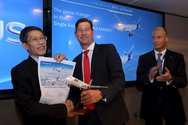 Chief Financial Officer Airbus Group Harald Wilhelm (C) and President of ST Aerospace Serh Ghee Lim (L) shake hands as Airbus Group CEO Tom Enders (R) looks on after they announced an agreement to convert aircraft from its best selling A320 family of single-aisle jets to freighters to boost the life of the planes, during the 51st Paris Air Show at Le Bourget airport near Paris June 17, 2015. REUTERS/Pascal Rossignol