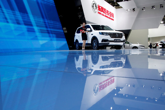 A woman stands next to Dongfeng motor group's SUV vehicle SX6 during the Auto China 2016 show in Beijing, China April 26, 2016. (Photo by Kim Kyung-Hoon/Reuters)