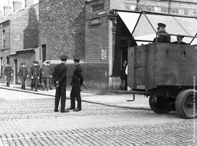 1932:  Belfast police patrol the streets with an armoured car following rioting  between the  unemployed and police leaving one man dead and 46 injured