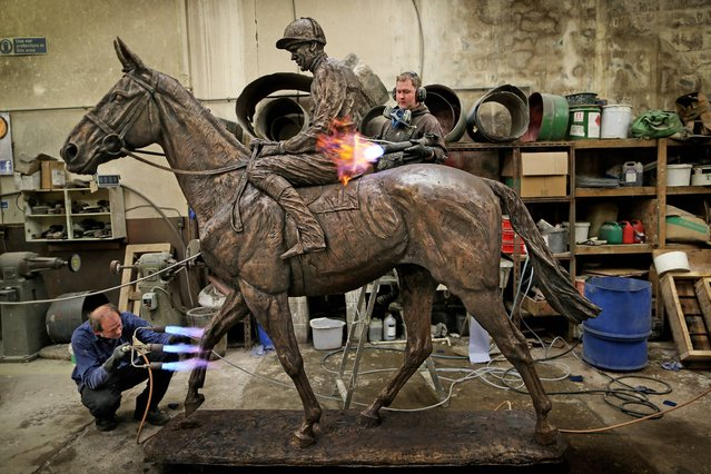 Christof Neuman (left) and Ciaran Patterson apply heat during the process of Patination in the Gaelic Street Bronze Foundry in Dublin to the lifesize statue of legendary racehorse Arkle with his trainer Pat Taaffe, on April 14, 2014.The most loved and celebrated horse in Irish history, Arkle will once more connect with the Irish people in a final gesture to mark the 50th anniversary of his Cheltenham Gold Cup win. Artist, Emma McDermott completed a life size bronze statue of Arkle, with the legendary jockey Pat Taafe astride him. (Photo by Julien Behal/Maxwells Dublin)