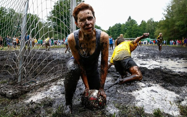Women compete for the ball in the mud during a swamp soccer game near the village of Dombrovka, Belarus on August 10, 2019. (Photo by Vasily Fedosenko/Reuters)