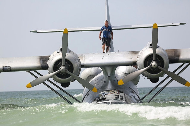 In this June 30, 2015 photo, a man stands on a vintage PBY-6A flying boat as it rests on the sandy bottom of the Gulf of Mexico just off the shore near Orange Beach, Ala. (Photo by Brian Kelly/Al.com via AP Photo)