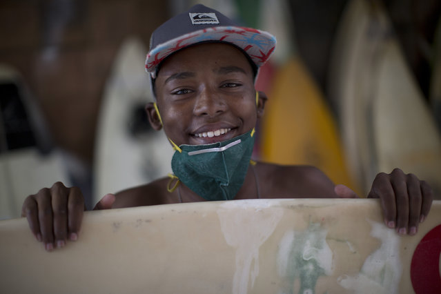 Robert Silva poses for a photo while fixing his board at the Rocinha Surf Association headquarters at Rocinha slum in Rio de Janeiro, Brazil, Thursday, July 2, 2015. Along with free surf boards and clothes, kids are taught how to maintain and fix their gear. (Photo by Felipe Dana/AP Photo)