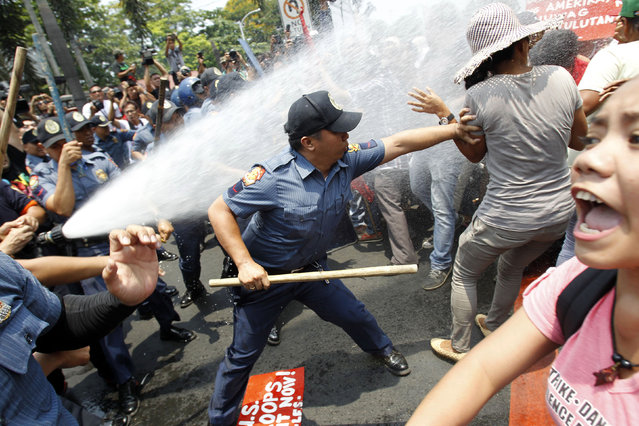 An anti-riot policeman reaches to grab a protester as they are hit with a water cannon during a protest against the upcoming visit of U.S. President Barack Obama next week, in front of the U.S. embassy in Manila April 23, 2014. (Photo by Romeo Ranoco/Reuters)