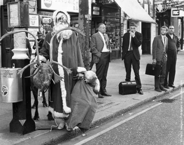 1970: Father Christmas waiting for a bus in the London West End with his reindeer and a sack of presents