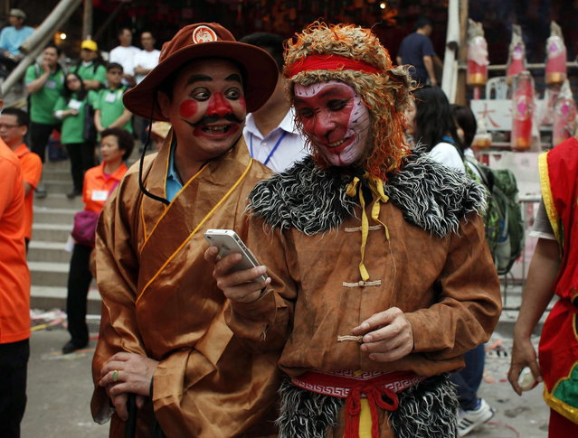 A man playing the role of Monkey King chats with his colleague while looking at a smartphone during Bun Festival parade at Hong Kong's Cheung Chau island May 6, 2014. The festival celebrates the islanders' deliverance from famine many centuries ago and is meant to placate ghosts and restless spirits. (Photo by Bobby Yip/Reuters)