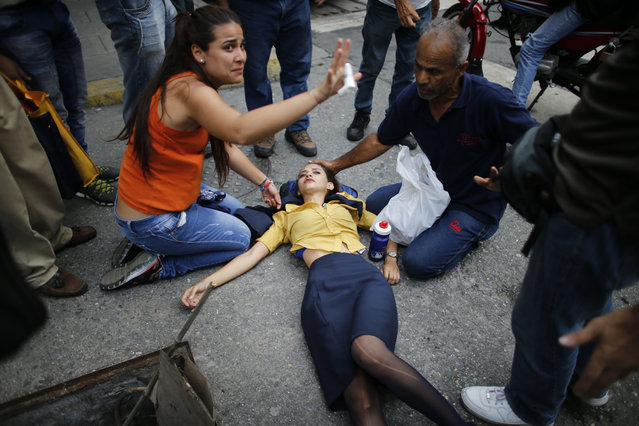 In this April 20, 2017 photo, a woman is aided by fellow demonstrators after falling, overcome by tear gas, during anti-government protests in Caracas, Venezuela. Tens of thousands of protesters asking for the resignation of President Nicolas Maduro flooded the streets again, one day after three people were killed and hundreds arrested in the biggest anti-government demonstrations in years. (Photo by Ariana Cubillos/AP Photo)