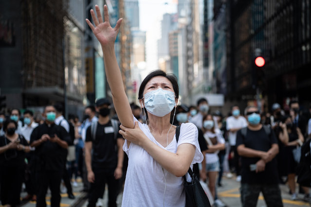 People protest a government ban on face masks in Central on October 4, 2019 in Hong Kong, China. Hong Kong's government invoked emergency powers on Friday to introduce an anti-mask law which bans people from wearing masks at public assemblies as the city remains on edge with the anti-government movement entering its fourth month. Pro-democracy protesters marked the 70th anniversary of the founding of the People's Republic of China in Hong Kong as one student protester was shot in the chest in the Tsuen Wan district during with mass demonstrations across Hong Kong. Protesters in Hong Kong continue to call for Chief Executive Carrie Lam to meet their remaining demands since the controversial extradition bill was withdrawn, which includes an independent inquiry into police brutality, the retraction of the word riot to describe the rallies, and genuine universal suffrage, as the territory faces a leadership crisis. (Photo by Laurel Chor/Getty Images)