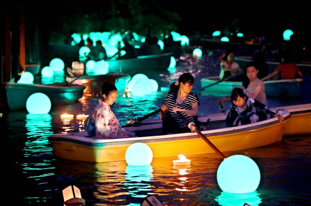 Visitors wearing a yukata, summer kimono, float lanterns during Chiyoda-ku Noryo no Yube, Lanterns floating event on the Chidorigafuchi moat of the Imperial Palace in Chiyoda Ward, Tokyo on July 13, 2015. People boarding boats enjoyed a magical and wondrous lights from 700 lanters and 100 green-color LED. (Photo by The Yomiuri Shimbun via AP Images)