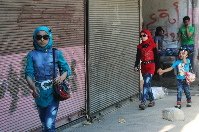Girls walk along a street on the first day of the Muslim holiday of Eid al-Fitr, which marks the end of the holy month of Ramadan, in a rebel-held area of Aleppo, Syria, July 17, 2015. (Photo by Abdalrhman Ismail/Reuters)