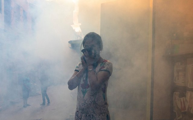 A local resident covers her faces as worker fumigates residential area to kill mosquitos in Kathmandu, Nepal, 05 September 2019. According to Epidemiology and Disease Control Division, at least 60 patients with dengue virus have been confirmed in Kathmandu. The dengue outbreak in Kathmandu is quite unusual and usually occurs in low belt eastern part of Nepal. (Photo by Narendra Shrestha/EPA/EFE/Rex Features/Shutterstock)