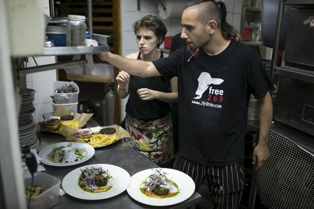 A cook wearing a T-shirt of an animal rights movement works in the kitchen of Georgian restaurant Nanuchka in Tel Aviv, Israel July 15, 2015. (Photo by Baz Ratner/Reuters)