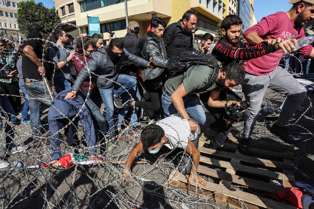 Lebanese protesters flee from security forces on their way back after having cut through the security barrier leading to the government palace at Riad al-Solh square in the capital Beirut's downtown district on November 19, 2019. An unprecedented protest movement against the ruling elite entered its second month with the country in the grip of political and economic turmoil. The leaderless pan-sectarian movement has swept the Mediterranean country since October 17, prompting the resignation of Prime Minister Saad Hariri's government. (Photo by Anwar Amro/AFP Photo)