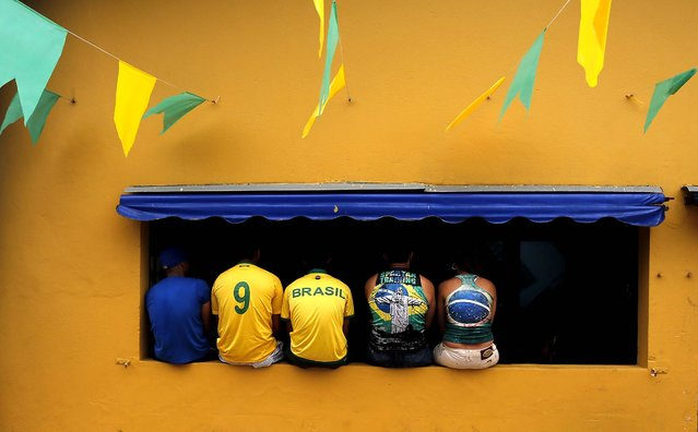 People watch the opening match in Porto Seguro, Brazil. (Photo by Matthias Schrader/Associated Press)