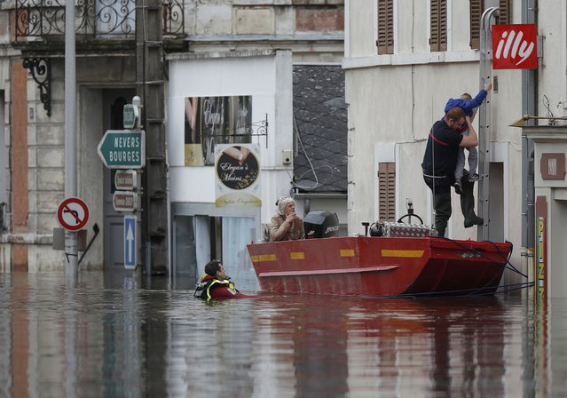 French firefighters use a small boat to evacuate residents from a flooded area after heavy rainfall in Montargis, near Orleans, June 1, 2016. (Photo by Christian Hartmann/Reuters)