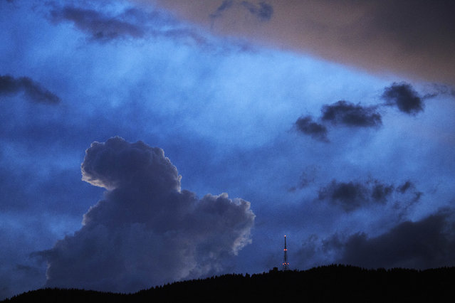 A radio and television broadcasting mast located at La Barillette in the Jura mountains is silhouetted by passing clouds as a stormy weather front moves across the region, as seen from Gingins, Switzerland, Friday, July 24, 2015. (Photo by David Azia/AP Photo)
