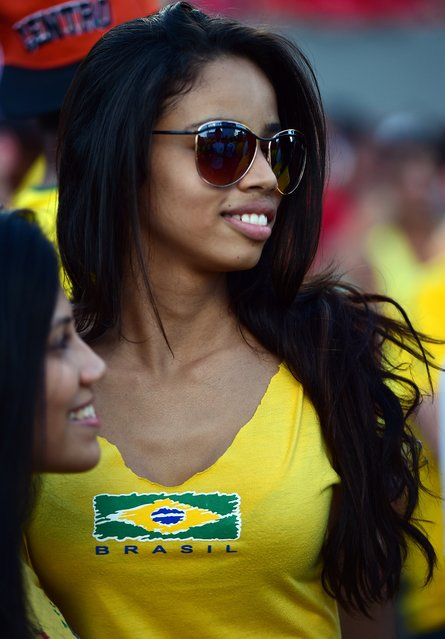 A Brazilian fan watches a live screening of her team's match against Croatia at the Fans Fest in Cuiaba, Brazil on June 12, 2014, as the 2014 FIFA World Cup inaugural Group A football match between Brazil and Croatia takes place at the Corinthians Arena in Sao Paulo. (Photo by Martin Bernetti/AFP Photo)