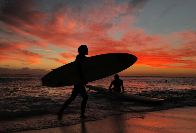 Surfers return to the shore as the sun sets over Waikiki in Hawaii, U.S. December 20, 2016. (Photo by Kevin Lamarque/Reuters)
