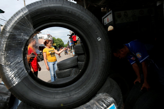 A Venezuelan woman looks for tires at a stall in Puerto Santander, Colombia, June 3, 2016. (Photo by Carlos Garcia Rawlins/Reuters)