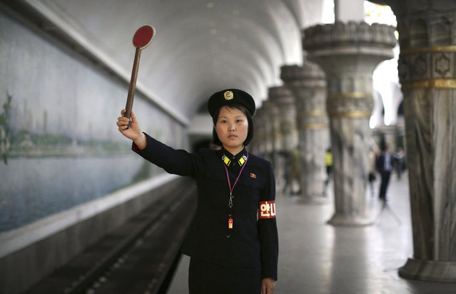 """In this May 7, 2016, photo, Pyongyang subway officer Ri Ok Gyong, 23, holds up a signal as she poses for a portrait in Pyongyang, North Korea. Ri has been working at the station for six years. She says that she is proud of her job because the subway station was one of the places where North Korean leader Kim Jong Un visited. When asked what's important to them, North Koreans might talk about working hard, or doing well at sports, or having a big family, but leader Kim Jong Un is never far from the conversation. Ri Ok Gyong's motto: """"I want to server people because Marshal Kim Jong Un loves his people and so must I"""". (Photo by Wong Maye-E/AP Photo)"""
