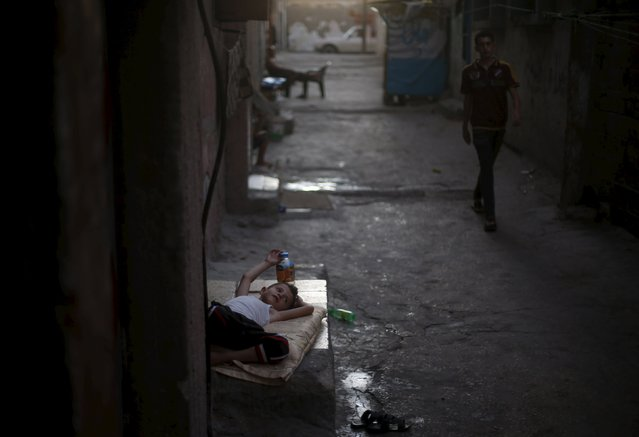 A Palestinian boy lies outside his family house to escape the heat during power cuts at Shatti (beach) refugee camp in Gaza City July 28, 2015. (Photo by Mohammed Salem/Reuters)