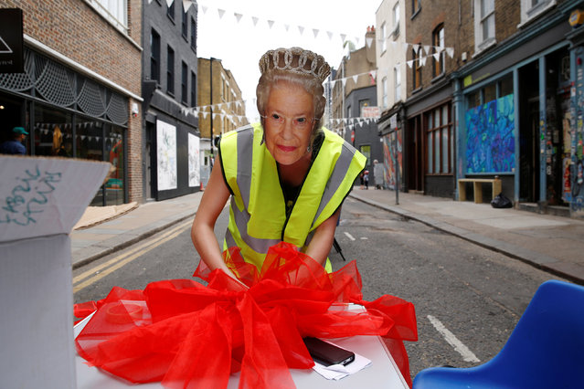 An organiser with a mask of Britain's Queen Elizabeth prepares ribbons and bows at the Redchurch Street Block Party, one of the many street parties this weekend to celebrate the Queen's 90th birthday at Shoreditch in London, Britain June 11, 2016. (Photo by Luke MacGregor/Reuters)