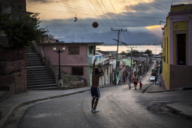 In this March 20, 2015 photo, a youth tosses a ball in a street that leads to the bay, in downtown Santiago, Cuba. (Photo by Ramon Espinosa/AP Photo)