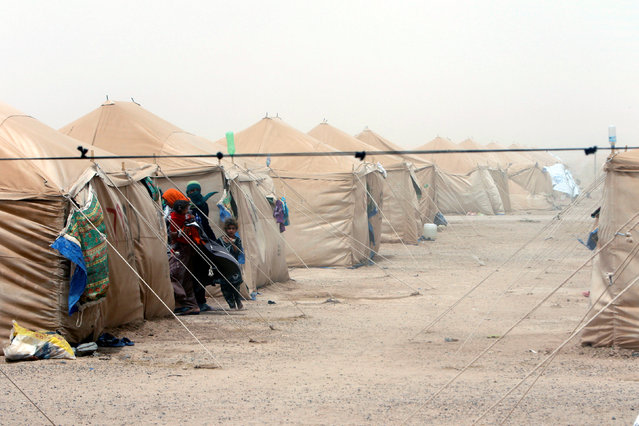 Displaced people, who fled from Falluja because of Islamic State violence, are seen during a dust storm at a refugee camp in Ameriyat Falluja, south of Falluja, Iraq, June 16, 2016. (Photo by Ahmed Saad/Reuters)
