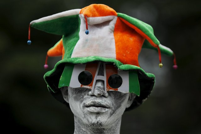 A man painted in the Ivory Coast flag colors looks on during the commemoration of Ivory Coast's 55th Independence Day in Abidjan, August 7, 2015. (Photo by Luc Gnago/Reuters)