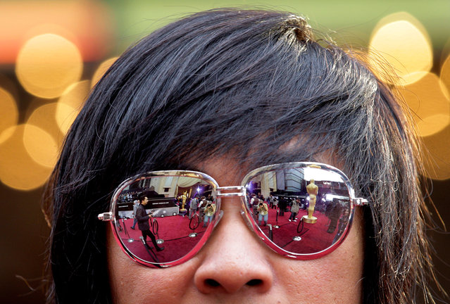The bustling scene on the red carpet is seen reflected in the sunglasses of actor Ple Nakorn Sirachai
