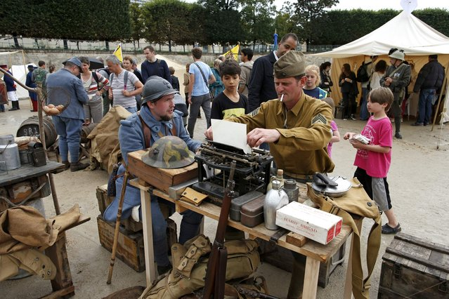 Men dressed in vintage American and French World War I military uniforms take part in a military camp reconstitution in the Tuileries Garden in Paris on the eve of Bastille Day, on Jule 14, 2014. (Photo by Benoit Tessier/Reuters)