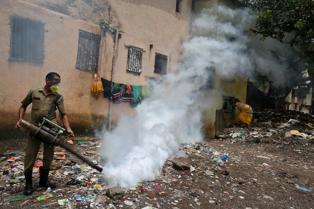 A municipal worker fumigates a slum area to prevent the spread of dengue fever and other mosquito-borne diseases in Mumbai, India, July 19, 2017. (Photo by Shailesh Andrade/Reuters)