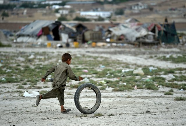 An Afghan Kochi nomad boy plays with a tire outside his tent on the outskirts of Kabul on August 2, 2015. (Photo by Wakil Kohsar/AFP Photo)