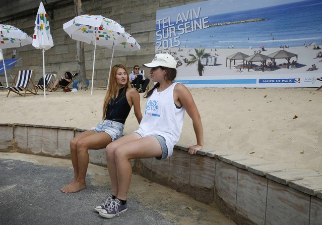 """Women stretch along an artificial sand beach at """"Paris Plages"""" near a giant photo promoting the """"Tel Aviv on Seine"""" event, in Paris, France, August 13, 2015. Paris' decision to celebrate Tel Aviv on Thursday in its annual beach-on-the-Seine festival has sparked much controversy, with leftist critics branding the event as """"indecent"""" following the death of a baby killed in an arson attack in the West Bank. (Photo by Pascal Rossignol/Reuters)"""