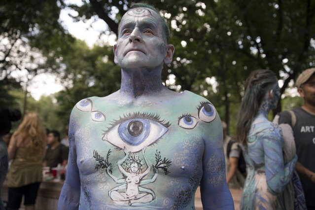 Jack van Riper, of New Jersey, stands for a photograph after being painted at Columbus Circle as body-painting artists gathered to decorate nude models as part of an event featuring artist Andy Golub, Saturday, July 26, 2014, in New York. Golub says New York was the only city in the country that would allow his inaugural Bodypainting Day. (Photo by John Minchillo/AP Photo)
