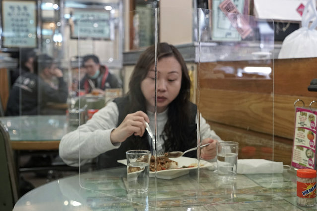 Customer has lunch with a transparent plastic panel setup on the table to isolate her from others in hopes of stopping the spread of the coronavirus in a Hong Kong, Wednesday, February 12, 2020. China's ruling Communist Party needs to make a politically fraught decision: Admit a viral outbreak isn't under control and cancel this year's highest-profile official event. Or bring 3,000 legislators to Beijing next month and risk fueling public anger at the government's handling of the disease. (Photo by Kin Cheung/AP Photo)