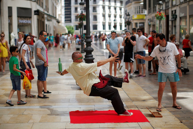 A street performer dressed up as a waiter performs for at Marques de Larios street in downtown Malaga, Spain, July 4, 2016. (Photo by Jon Nazca/Reuters)