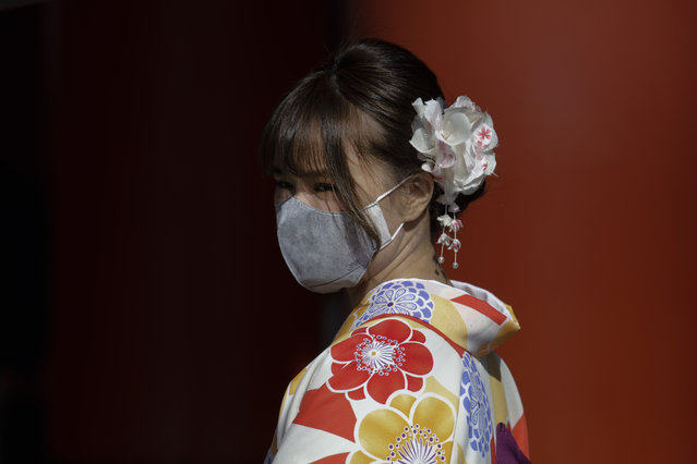A tourist pauses for photos with her mask on at Sensoji Temple Thursday, January 30, 2020, in Tokyo. The country began evacuating Japanese citizens on Wednesday from the Chinese city Wuhan hardest-hit by the virus. (Photo by Jae C. Hong/AP Photo)