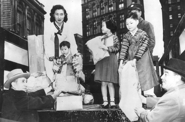 Grover Whalen, right, chairman of the Korea Clothes Drive, donating a bag of clothes to be sent to Korean war victims, 22nd November 1951. (Photo by Keystone)