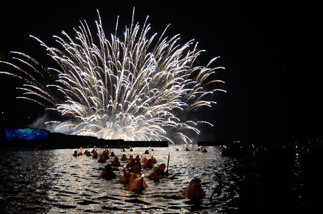 Fireworks show over a port during the day one of the Ama Matsuri festival on July 16, 2016 in Minamiboso, Japan. During the Shirahama Ama Matsuri, or Shirahama Female Diver Festival, people participate in a parade of portable shrines, the dance of dragon gods, and the all-female, night-time diving. More than 50 people participated in the highlight of the festival, the night-time diving where the female divers swim with all-white clothing and torches to reenact the rescue operation of a ship-wreck from long ago. The festival sends prayers for gifts from the sea, hopes for peace, and pays respects to all those who have died in the ocean. (Photo by Takashi Aoyama/Getty Images)