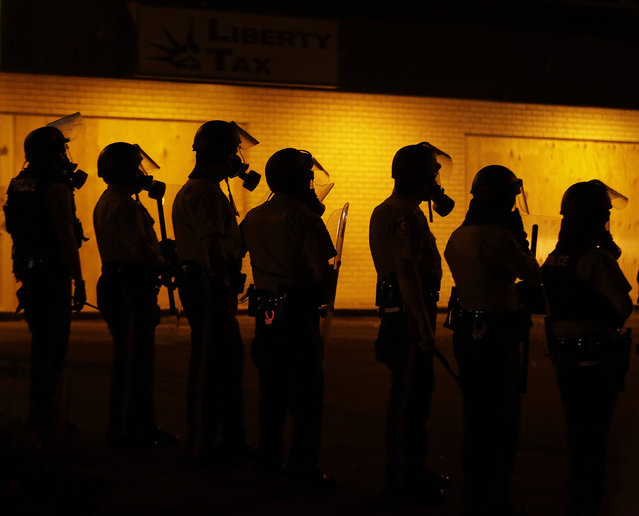 Police wait to advance after tear gas was used to disperse a crowd Sunday, August 17, 2014, druing a protest for Michael Brown, who was killed by a police officer last Saturday in Ferguson, Mo. As night fell Sunday in Ferguson, another peaceful protest quickly deteriorated after marchers pushed toward one end of a street. Police attempted to push them back by firing tear gas and shouting over a bullhorn that the protest was no longer peaceful. (Photo by Charlie Riedel/AP Photo)