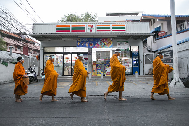 Buddhist monks wear face shields amid concerns over the spread of the COVID-19 as they collect alms on April 1, 2020 in Bangkok, Thailand. Thailand has more than 1,500 confirmed COVID-19 cases and has entered a state of emergency in order to take stronger measures against the spread of the virus. (Photo by Allison Joyce/Getty Images)