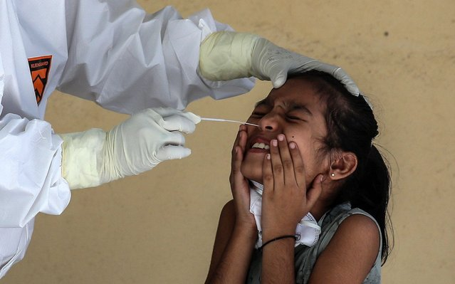 An Indian medical staff in protective gear collects a nasopharyngeal swab sample from a girl who resides in a quarantine building in Mumbai, India, 07 April 2020. Indian Prime Minister Modi has declared a nationwide 21-day lockdown across India, starting on 24 March 2020 to stem the widespread of the SARS-CoV-2 coronavirus which causes the COVID-19 disease. (Photo by Divyakant Solanki/EPA/EFE)