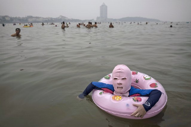 A Chinese girl wears a face-kini as she floats in the water on August 21, 2014 on the Yellow Sea in Qingdao, China. The locally designed mask is worn by many local women to protect them from jellyfish stings, algae and the sun's ultraviolet rays. (Photo by Kevin Frayer/Getty Images)