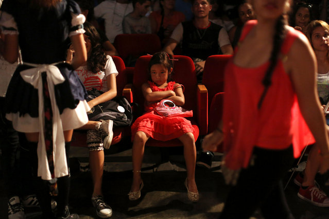 A child watches performances during the Cuban Otaku festival at a cinema in Havana, Cuba, July 24, 2016. (Photo by Alexandre Meneghini/Reuters)